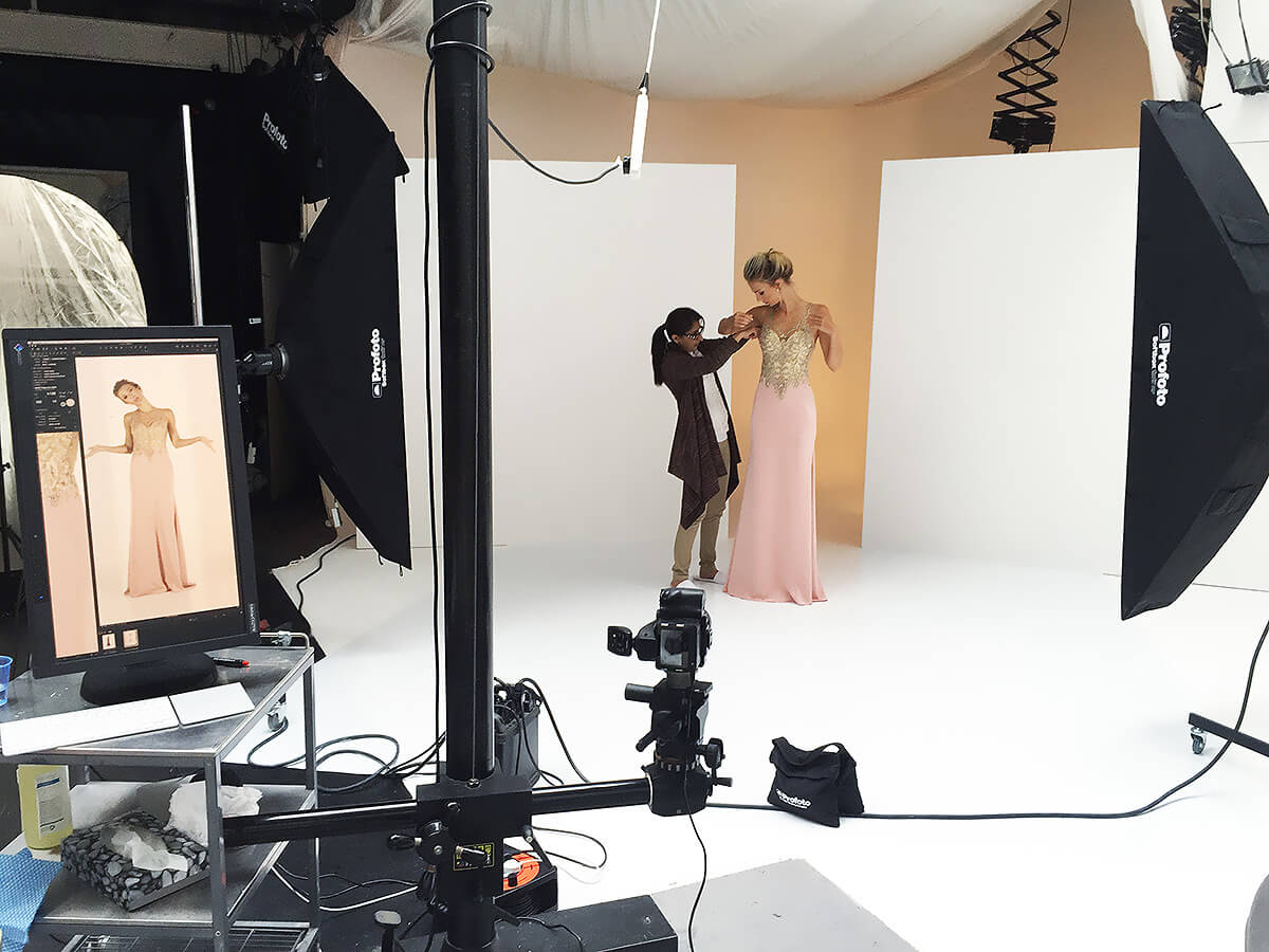 Fashion photographer pictured with professional model during studio photography shoot